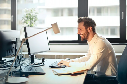 Smiling employee using his computer